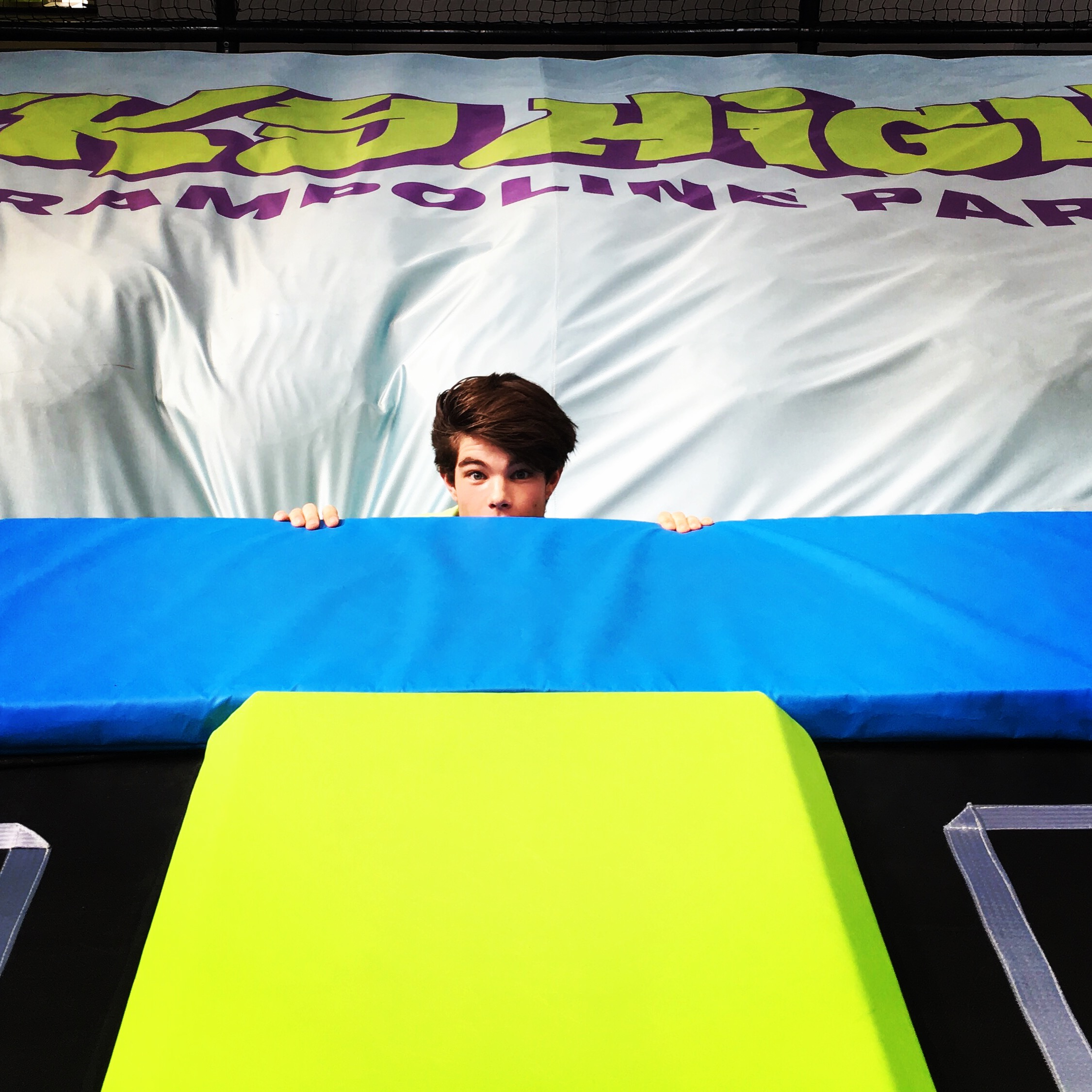 Boy peeking over air bag at Sky High Trampoline Park in Sussex
